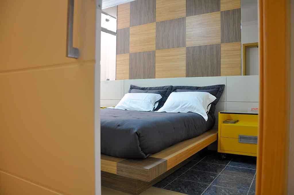 cama de casal feita sob medida e painel de madeira